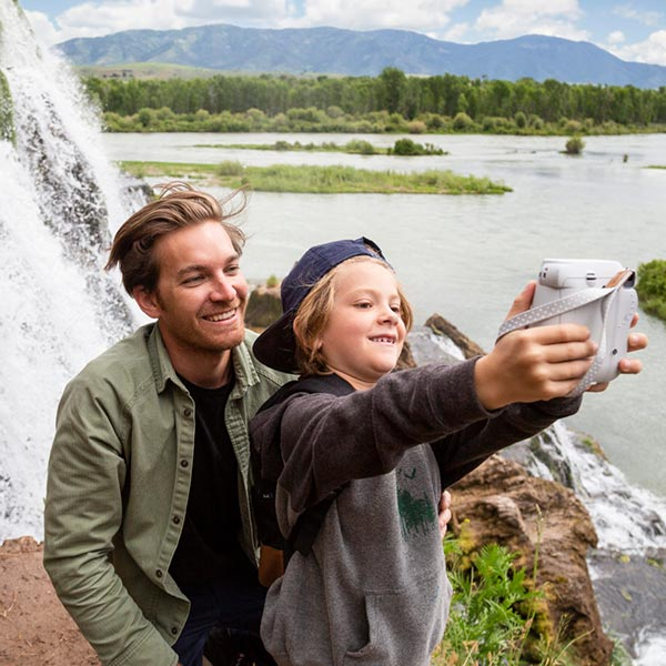 Father and child taking a selfie in front of waterfall